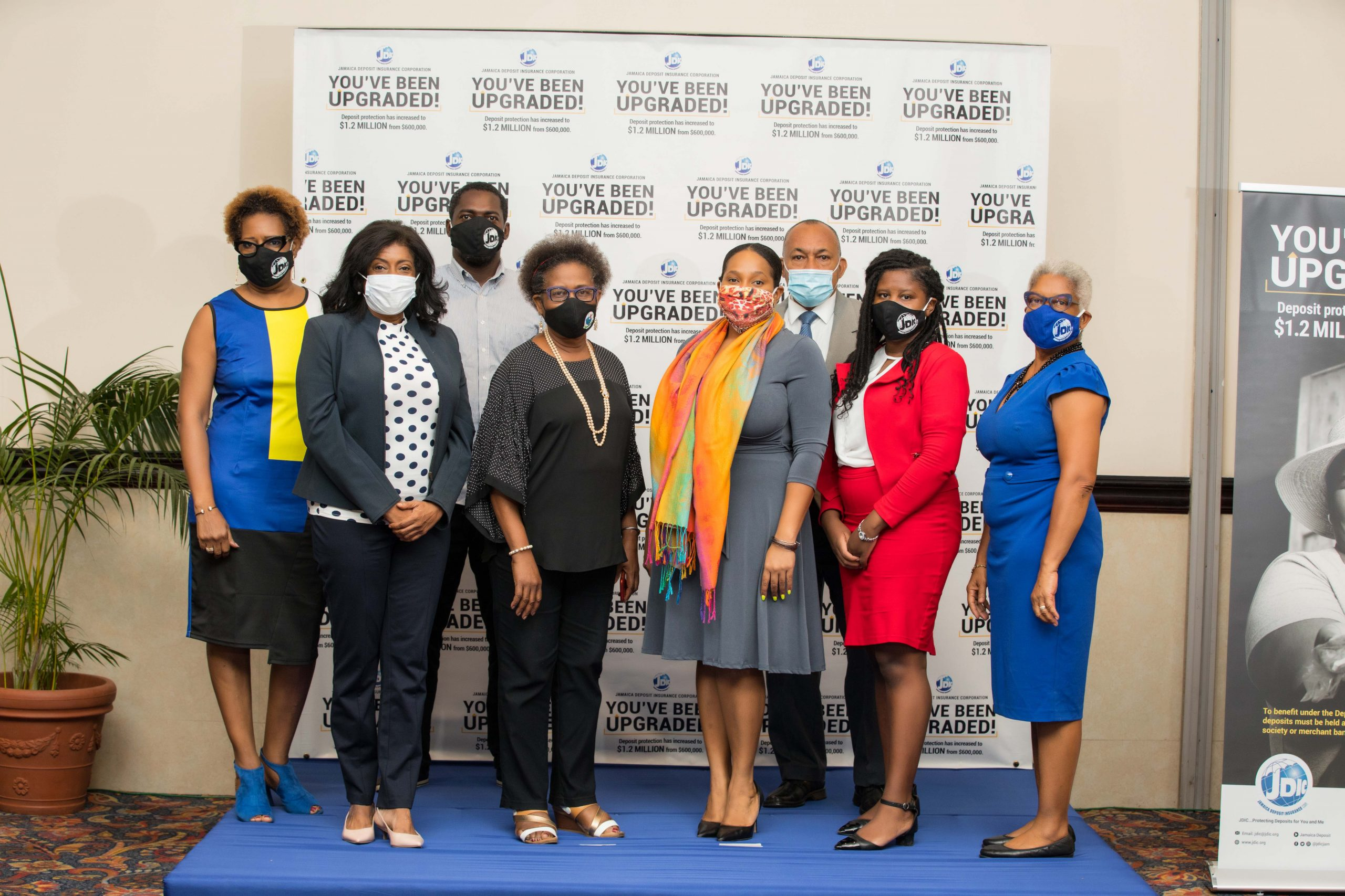 JDIC team members along with (L-R) Antoinette McKain, CEO, JDIC and Myrtle Halsall, OD, Board Chairman pause for a team photo opp at the JDIC's You've Been Upgraded Digital Townhall.