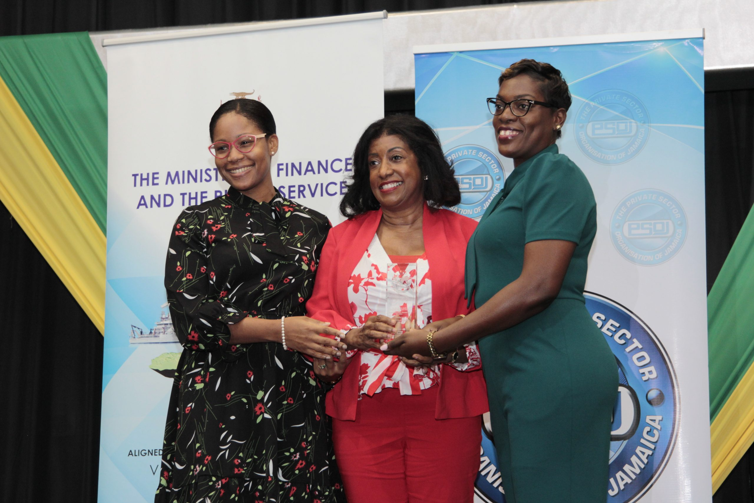 JDIC's General Counsel and Corporate Secretary, Stacie Ann Carty and CEO Antoinette McKain accept the award for Best Board Composition, Function and Structure from Cornella Alladice, Corporate Relationship Manager, NCB at the Public Sector Corporate Governance Awards 2019.